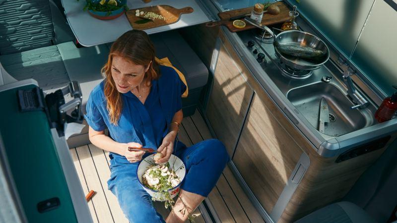 Kvinna sitter framför köket i VW California campingbil