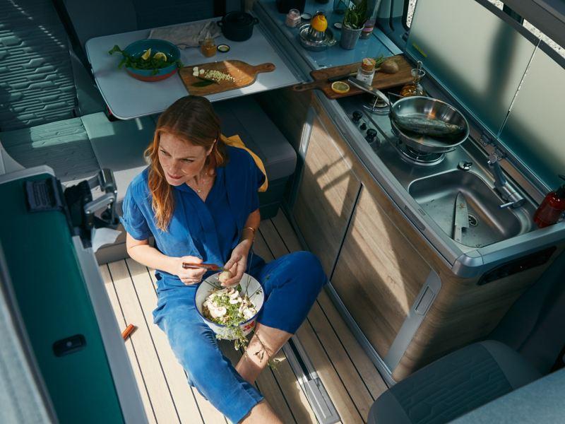 Eine Frau sitzt auf dem Boden einer Küche in einem Wohnmobil und schneidet Salat.