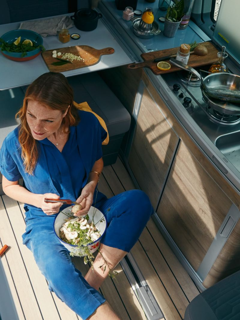 A woman is sittig on the floor next to the kitchen in a California 6.1 preparing salad.