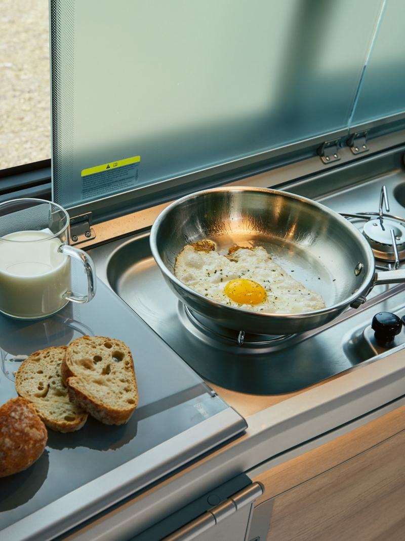 A pan with a fried egg on a gas stove.