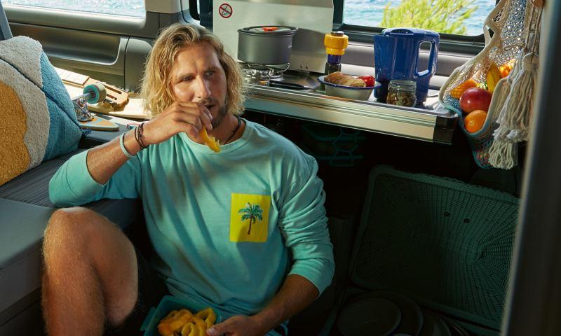 Eine Person sitzt in der Miniküche eines California 6.1 Beach.