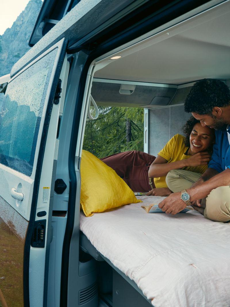 Mężczyzna i kobieta w Volkswagen California 6.1 w górskim krajobrazie.