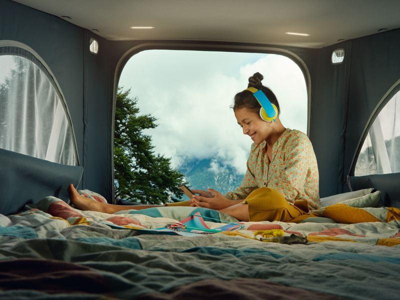 Dziecko siedzi w części sypialnej podnoszonego dachu Volkswagen California 6.1.