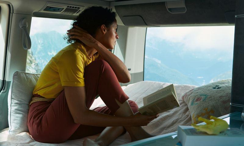 Kobieta siedzi na łóżku Volkswagen California i spogląda na zewnątrz.