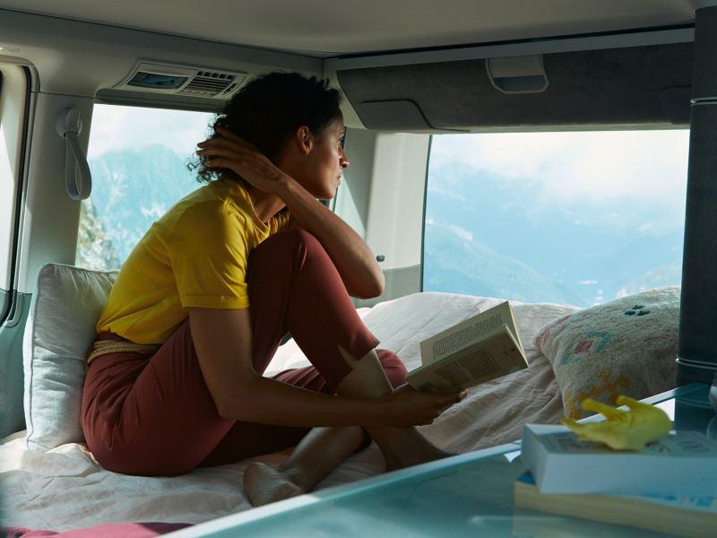Eine Frau sitzt auf der Schlafmöglichkeit eines VW California und schaut ins Freie.