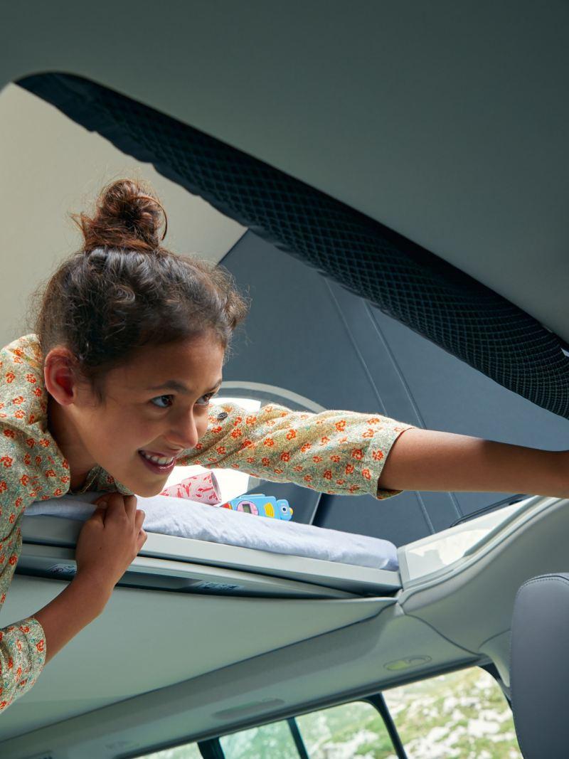 Dziecko obsługuje panel obsługowy, w podnoszonym dachu Volkswagen California 6.1.