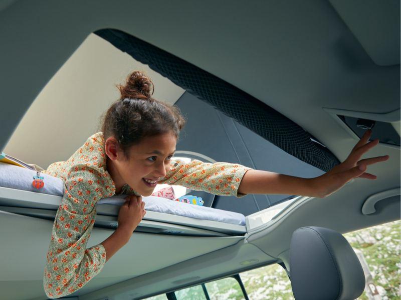 Ein Kind bedient eine Multifunktionseinheit, während es  im Aufstelldach des VW California liegt.
