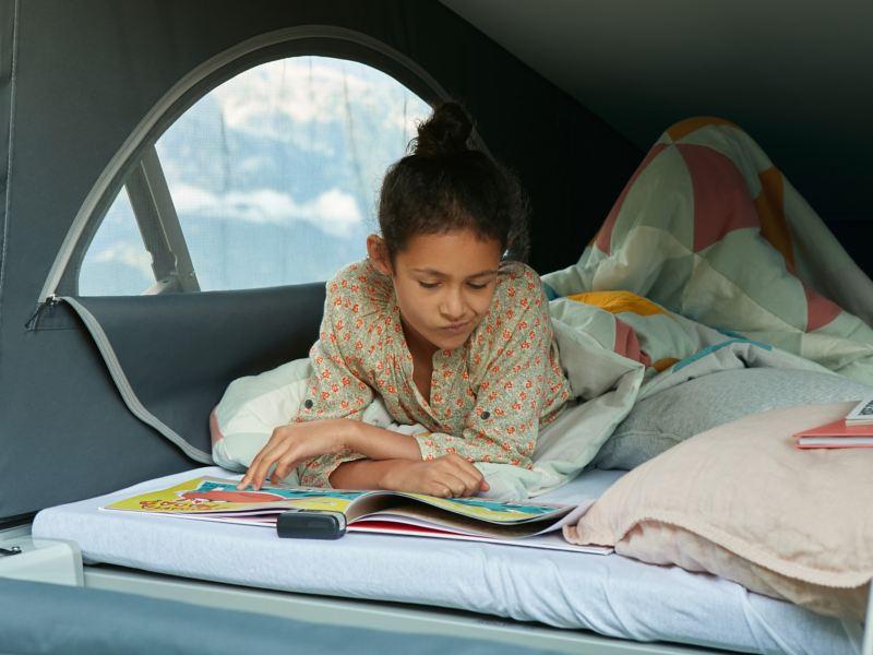 Ein Kind liegt in der Schlafmöglichkeit eines VW California.
