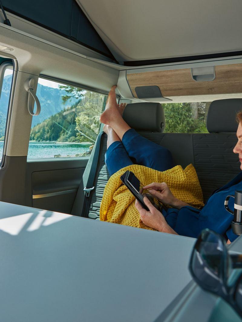 Kobieta siedzi wygodnie we wnętrzu Volkswagen California 6.1.