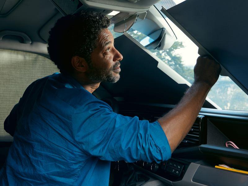 Mężczyzna przyciemnia przednie okno samochodu Volkswagen California 6.1 za pomocą żaluzji.
