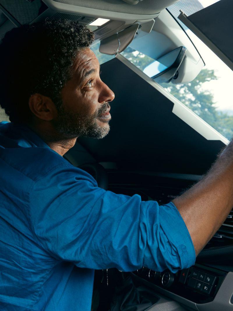 Ein Mann verdunkelt die Frontscheibe eines VW California von Innen per Jalousie.