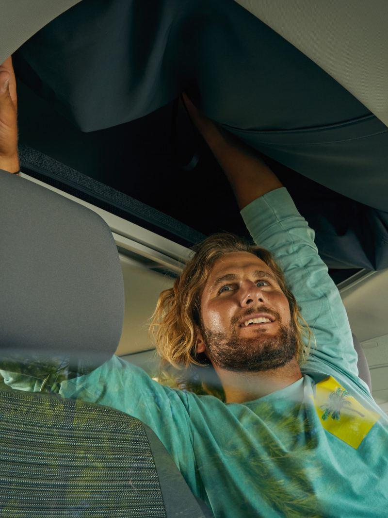 Mężczyzna otwiera ręcznie podnoszony dach Volkswagen California 6.1 Beach.