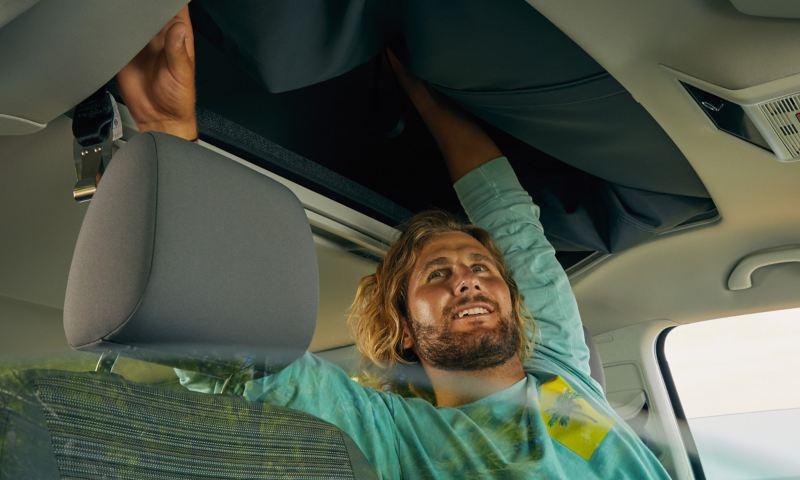 Eine Person öffnet das manuelle Aufstelldach eines California 6.1 Beach.