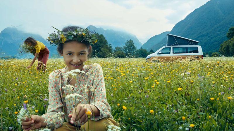 Ein Kind mit einer Blumenkrone in einem Blumenfeld.