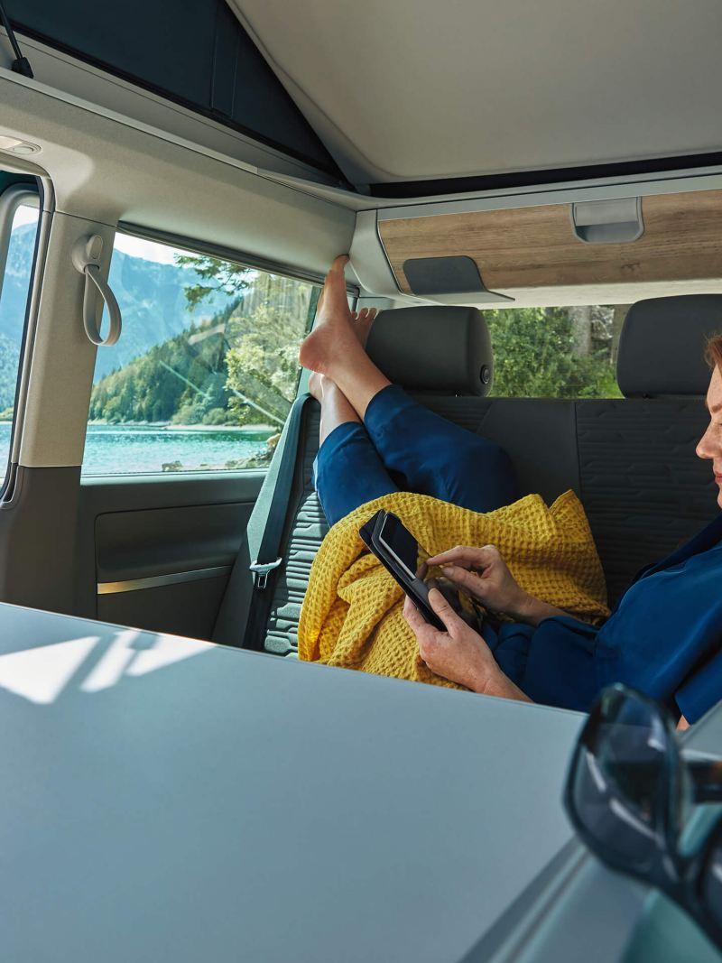 Eine Frau hat es sich im Innenraum eines VW California gemütlich gemacht.