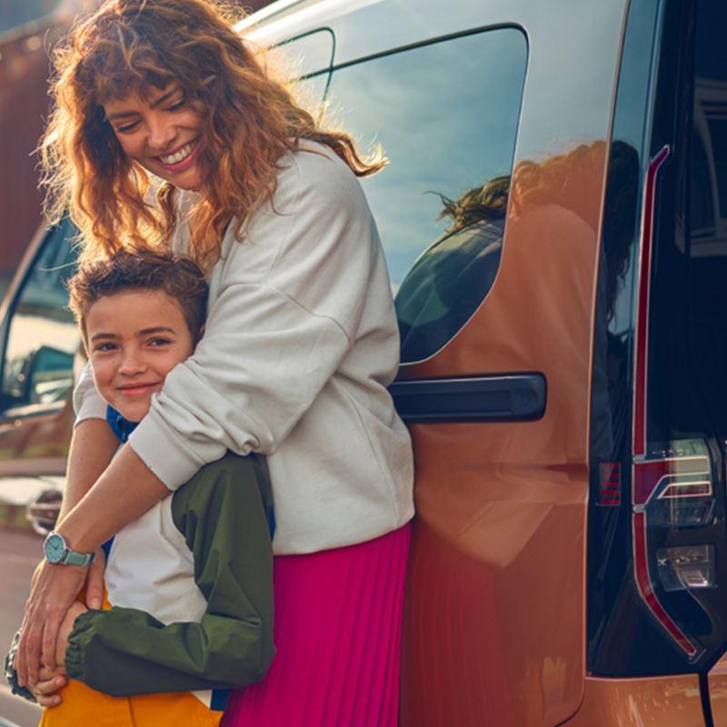Une femme et un jeune garçon se tenant devant le nouveau Volkswagen Caddy.