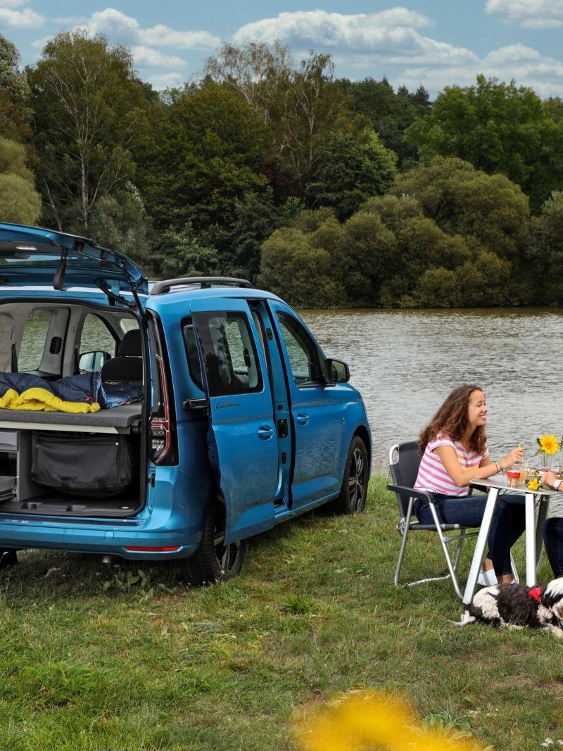 Dwie kobiety przy stoliku campingowym obok Caddy California