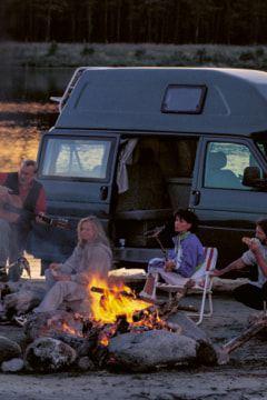 Eine Gruppe Menschen macht abends ein Lagerfeuer vor dem Volkswagen Nutzfahrzeuge California. Das Fahrzeug steht am Strand. Direkt dahinter beginnt das Meer.