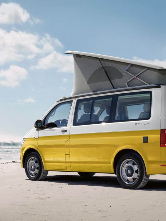 Ein gelber Volkswagen Nutzfahrzeuge California steht bei sonnigem Wetter am Strand. Zwei Surfer laufen darauf zu.