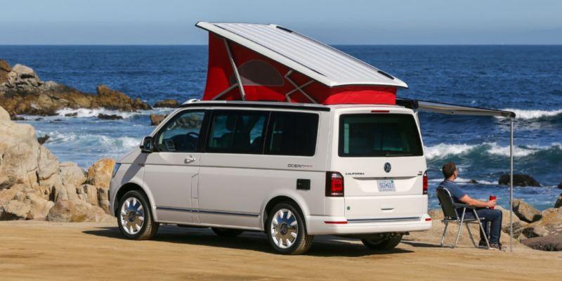 Ein Volkswagen Nutzfahrzeuge California mit Hochdach und ausgefahrener Markise steht auf einer Wiese. Der Fahrer sitzt darunter auf einem Campingstuhl und betrachtet den Sonnenuntergang.