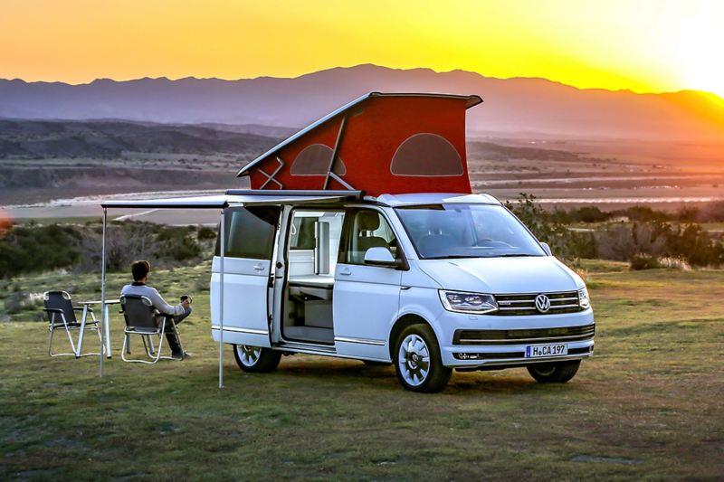 Uma California da Volkswagen Veículos Comerciais com tejadilho elevado e toldo estendido num prado. O condutor sentado numa cadeira de campismo observa o pôr-do-sol.