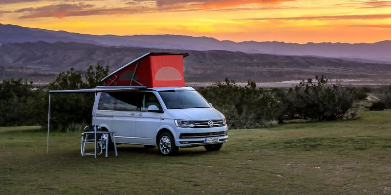 Uma California da Volkswagen Veículos Comerciais com tejadilho elevado e toldo estendido num prado. Ao fundo vemos o pôr-do-sol.