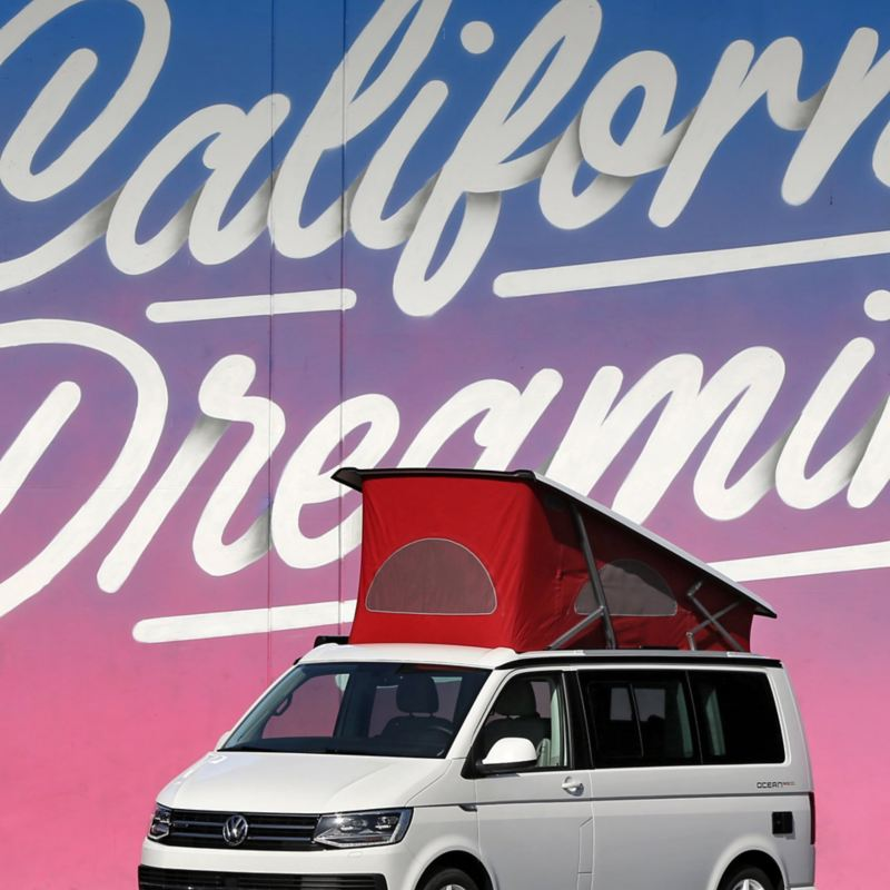 """Ein Volkswagen Nutzfahrzeuge California mit Hochdach steht vor dem illustrierten Schriftzug """"California Dreaming""""."""