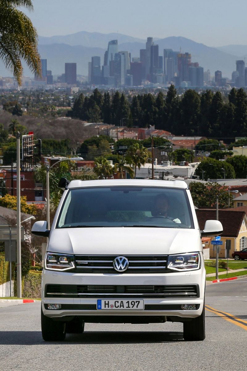 Ein Volkswagen Nutzfahrzeuge California fährt eine kalifornische Straße entlang.