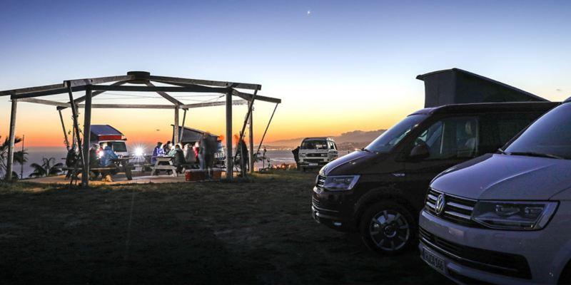 Mehrere unterschiedliche Volkswagen Nutzfahrzeuge California-Modelle stehen bei Sonnenuntergang an einer Küste. Im Hintergrund kann man das Meer erahnen.
