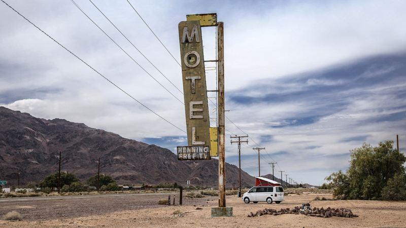 """Der Volkswagen Nutzfahrzeuge California hält hinter einem großen """"Motel""""-Schild an einem kalifornischen Highway."""