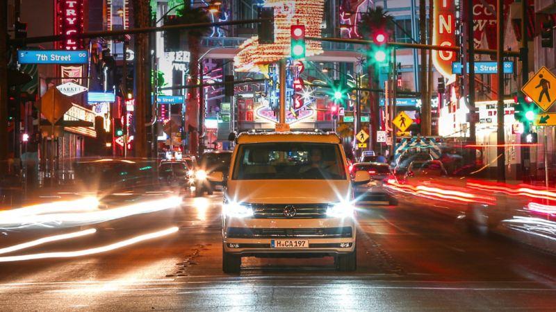 Der Volkswagen Nutzfahrzeuge California fährt durch eine kalifornische Innenstadt. Um ihn herum funkeln bunte Leuchtreklamen.