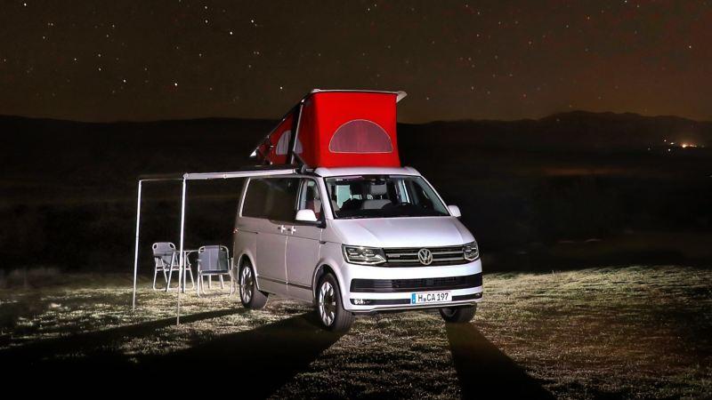Der Volkswagen Nutzfahrzeuge California steht bei Nacht auf einer Wiese. Die Markise ist ausgefahren. Darunter stehen Campingmöbel.