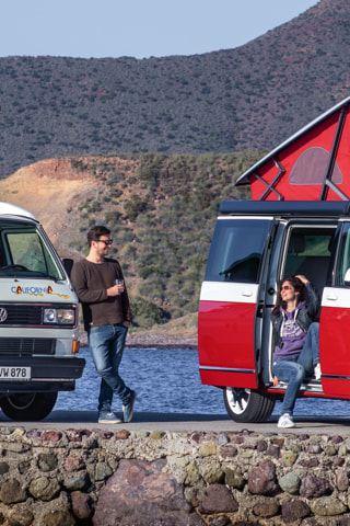 Zwei Volkswagen Nutzfahrzeuge California mit Hochdach stehen auf einer Mole am Meer.