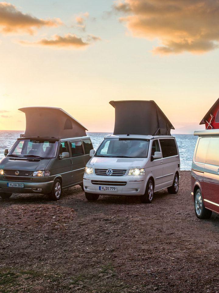 Vier Volkswagen Nutzfahrzeuge California unterschiedlicher Generationen stehen bei Sonnenuntergang am Strand.