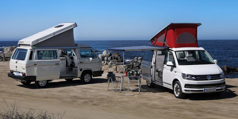 Zwei Volkswagen Nutzfahrzeuge California mit Hochdächern stehen an einem felsigen Strand. Beim rechten Fahrzeug ist die Markise ausgefahren. Darunter stehen Campingmöbel.