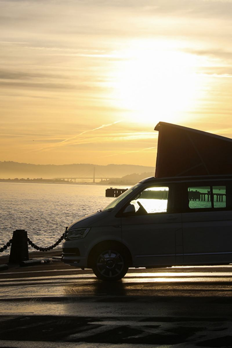 A California da Volkswagen Veículos Comerciais em contra-luz ao pôr do sol numa estrada costeira à beira-mar.