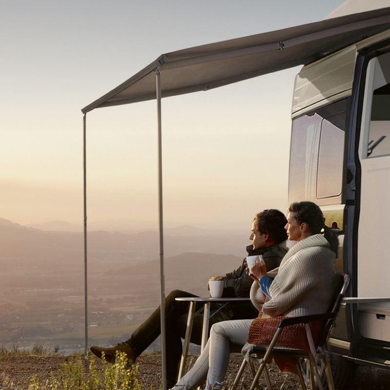 Ein Pärchen sitzt vor der Studie des California XXL. Sie betrachten den Sonnenaufgang.