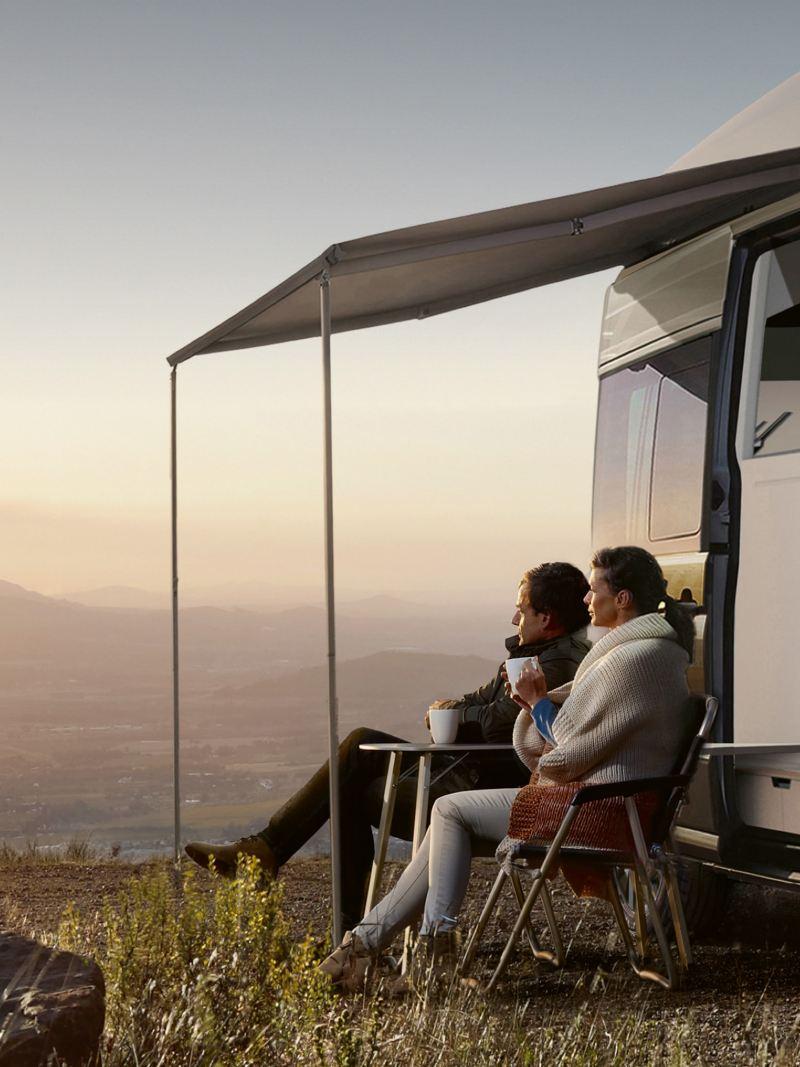 Um par de namorados sentados à frente da Grand California. Contemplam o nascer do sol.