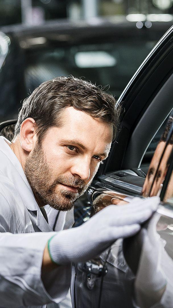 Volkswagen-Mitarbeiter fährt mit seiner Hand prüfend über die Seite eines Volkswagen