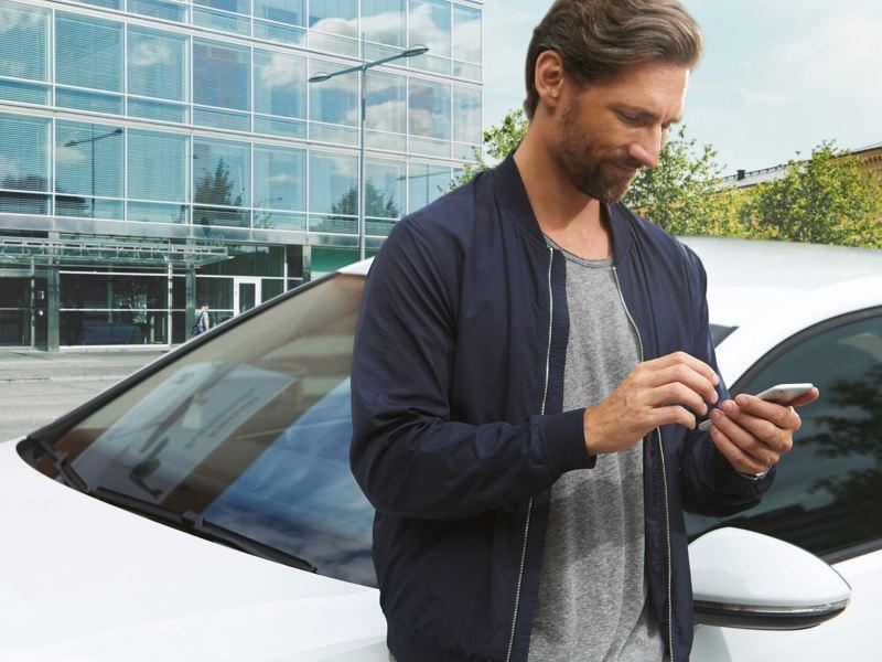 Man using smartphone in front of Volkswagen car