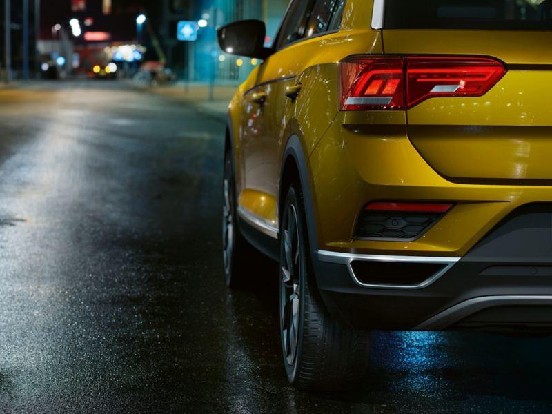Rear shot of a yellow Volkswagen T-Roc, on a dark brick road