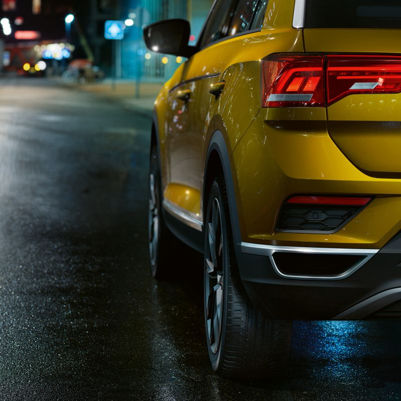 Rear shot of a yellow Volkswagen T-Roc, on a dark brick road.