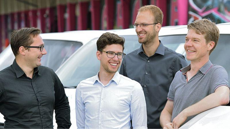 Die Gründer von CarlundCarla.de stehen neben einem ihrer Volkswagen Nutzfahrzeuge Transporter.