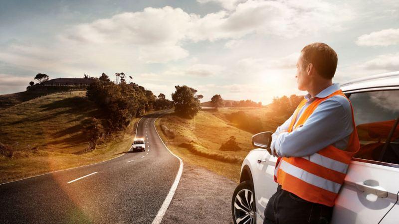 Un uomo che indossa il gilet ad alta visibilità è appoggiato ad una Volkswagen in attesa del servizio di soccorso stradale