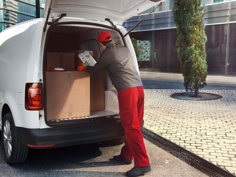 The rear of a white VW Caddy Panel Van with an open boot viewed at an angle. A man in a delivery driver's uniform is loading large packages.
