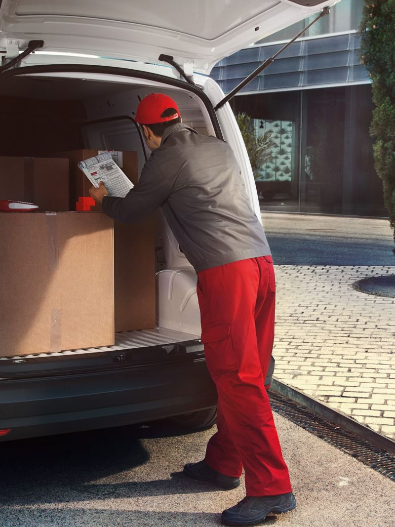 The rear of a white Caddy Delivery Van with an open boot viewed at an angle. A man in a delivery driver's uniform is loading large packages.