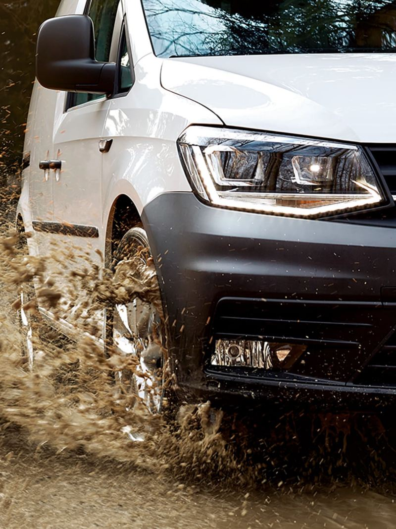 A white Caddy Kombi drives dynamically over muddy terrain. The water from a big puddle splashes far into the air.