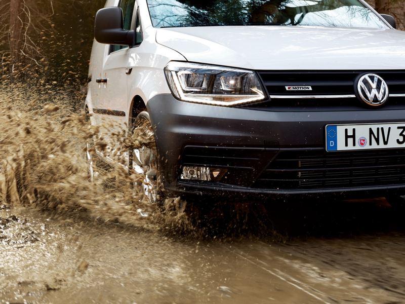 Een witte Caddy stationwagen rijdt dynamisch over modderige grond. Het water uit een grote plas schiet omhoog. Door de 4Motion vierwielandrijving presteert de Caddy volkswagen optimaal op alle soorten ondergronden.