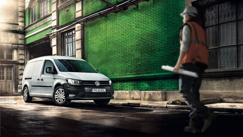 Volkswagen Caddy Furgon zaparkowany przy budynku.