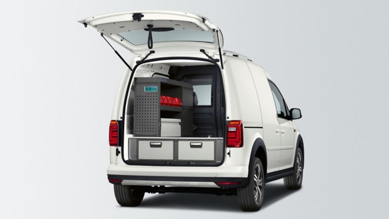 Ein weißer umgebauter Caddy Kastenwagen Alltrack mit offenem Kofferraum von hinten.